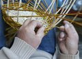 Expert hands of craftsman creates a woven wicker basket Royalty Free Stock Photo