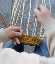 Expert hands of the elderly craftsman creates a woven wicker bas Royalty Free Stock Photo