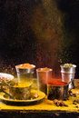 Exploding of spices set pepper turmeric anise coriander in vintage metal cups over black background Stock Photography