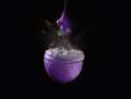 Exploding water balloon an purple party filled with Royalty Free Stock Photos