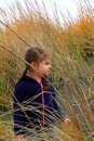 Exploring beach grass a cute little year old girl with dark pigtails in tall Royalty Free Stock Images