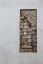 Exposed bricks in a wall that has been rendered Royalty Free Stock Photo