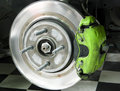 Exposed disk brake with caliper front wheel axle of a car metallic and attached green Royalty Free Stock Photography