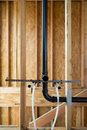 Exposed new home construction interior view of with plumbing and wood studs with selective focus Royalty Free Stock Image