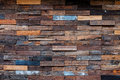 Exposed wooden wall exterior patchwork of raw wood forming a beautiful parquet wood pattern Royalty Free Stock Photo