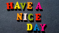The expression `Have a nice day` made of colorful wooden letters on a dark table. Royalty Free Stock Photo