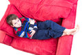 Expression mischievousness eight years old boy with arms closed on the couch by looking up in to your eyes isolated on white Stock Image
