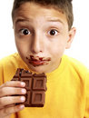 Expressive child eating chocolate Royalty Free Stock Photo