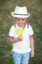 An expressive child in a hat holding candy on a garden background. Curious boy with a green lollipop. Kids with sweets. Royalty Free Stock Photo