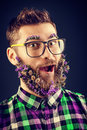 Expressive face young man in glasses and a beard of flowers Royalty Free Stock Image