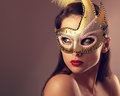 Expressive female model posing in carnival mask with red lipstick and looking vamp on empty copy space background. Closeup Royalty Free Stock Photo