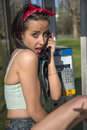 Expressive girl with phone talking by public telephone Royalty Free Stock Images