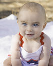 Expressive happy baby girl a cute smiling with big blue eyes sits on a blanket in the park wearing red white and blue Royalty Free Stock Photos