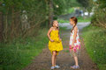 Expressive little girl tells her sister standing in the Park. Walking. Royalty Free Stock Photo