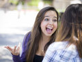 Expressive young mixed race female sitting and talking with girl attractive student girlfriend outside on bench Stock Photo