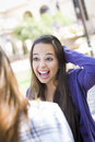 Expressive young mixed race female sitting and talking with girl attractive student girlfriend outside on bench Stock Photography