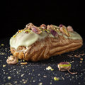 Exquisite cream dessert eclair with pistachios with crumbs on the background Royalty Free Stock Photography