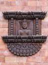 Exquisite old wood carving of hindu god Vishnu on soft pink brick wal Royalty Free Stock Photo