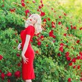 Exquisite Valentines Day background. Young slim retro girl with red lips in stylish dress in beautiful summer roses garden.
