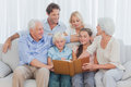 Extended cheerful family looking at a photo album in living room Royalty Free Stock Image