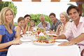 Extended family group enjoying outdoor meal together Stock Photos