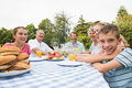 Extended family having dinner outdoors at picnic table smiling camera Stock Image