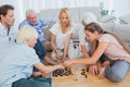 Extended family playing chess in the living room Stock Photography