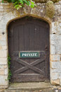 Exterior door with private sign weathered set in a buff coloured stone wall has Stock Photography