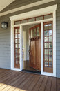 Exterior shot of an open wooden front door vertical upscale home with windows Stock Image