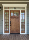 Exterior shot of a wooden front door vertical an upscale home with windows Royalty Free Stock Photography