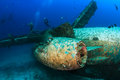 Exterior of an underwater aircraft wreck scuba divers explore the wreckage a sunken airplane Stock Photos