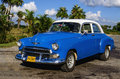 Exterior view of thclassic american blue car one of streets in havana e typical cuban vegetable and fruit shop in cuba classic Stock Photo