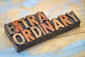 Extraordinary word in wood type abstract vintage letterpress printing blocks stained by color inks Royalty Free Stock Image