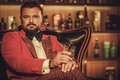 Extravagant stylish man with whisky glass sitting on armchair in Royalty Free Stock Photo
