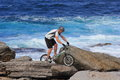 Extreme biking man on rocky shore a trains his skills the Royalty Free Stock Image