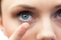 Extreme close up on gorgeous model applying contact lens her blue eyes Stock Image