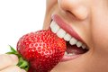 Extreme close up of teeth biting strawberry. Royalty Free Stock Photo