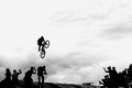Extreme cyclists, young man doing jump with bmx bike on background of black and white silhouette and clouds Royalty Free Stock Photo