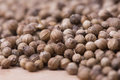 Extremely close up of coriander seeds on a wooden countertop Stock Photos