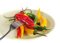 Extremely dinner red yellow and green pepper on a plate are isolated on the white Royalty Free Stock Image