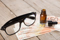 eye care concept - reading glasses, eye drops and money Royalty Free Stock Photo