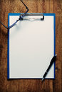 Eye-glasses and a black pen on an empty white page Royalty Free Stock Photo
