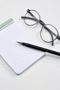 Eye glasses blank notepad and mechanical pencil on the table Stock Photography