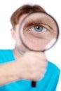 Eye of man, looking through magnifying glass Royalty Free Stock Photo