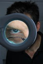 Eye portrait of a man behind magnifying lens Stock Image