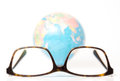 Eyeglasses and globe blurred at the back on white Stock Photography