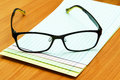 Eyeglasses and note paper on wooden office table background Stock Photo