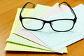 Eyeglasses and note paper on wooden office table background Royalty Free Stock Photography