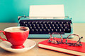 Eyeglasses over notebook, coffee cup and typewriter Royalty Free Stock Photo