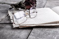 Eyeglasses and rose on old notebook close up Royalty Free Stock Photos